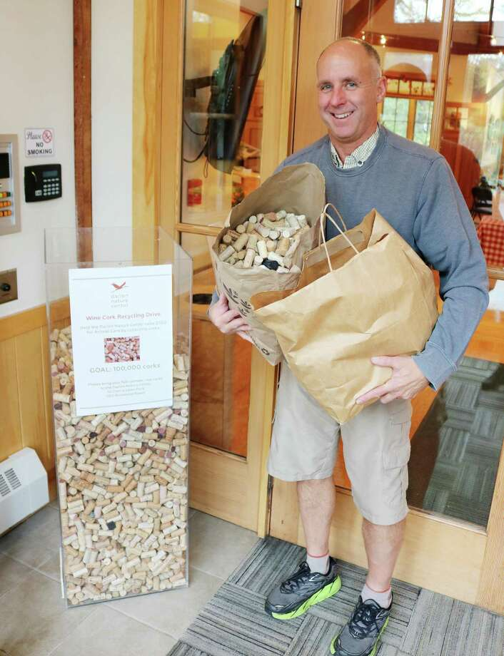 Tim Smith, of WinePort of Darien, drops off hundreds of corks for the Darien Nature Center, which is collecting them during the holiday season. Photo: Contributed Photo