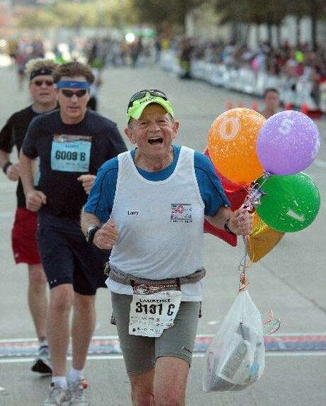 Larry Macon, center, a trial attorney from San Antonio, holds balloons after crossing the finish line of the Dallas White Rock Marathon in Dallas on Sunday, Dec. 14, 2008. Macon broke his own world record with this, his 105th marathon of the year. Photo: Rex C. Curry /Dallas Morning News