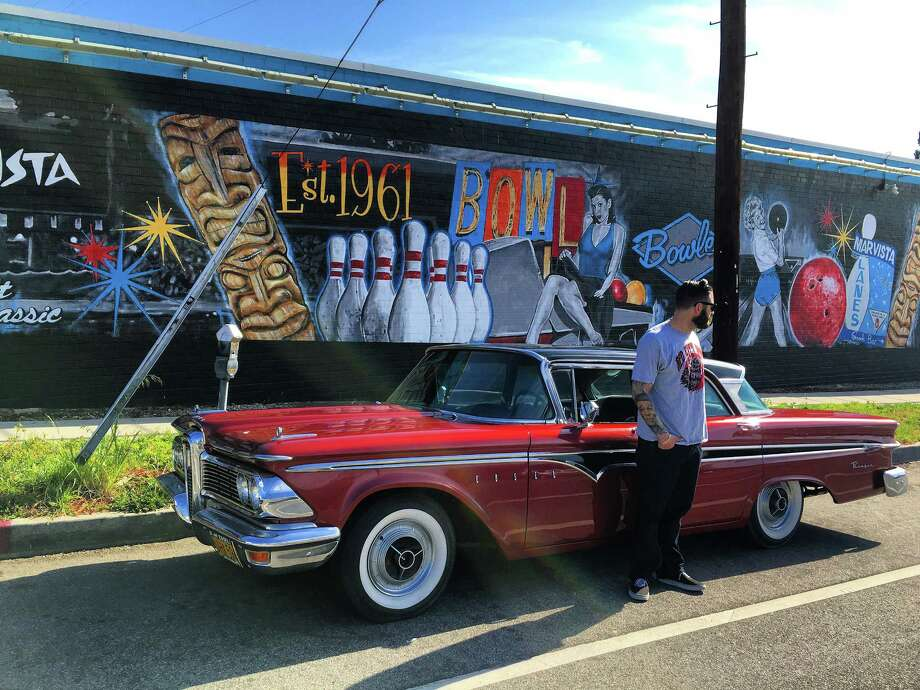 Jonas Never shows his artistic work with his 1959 Edsel Ranger in front of the bowling alley mural in Mar Vista, California. Photo:  Courtesy Of Mike Hayden