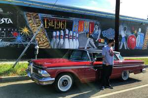 Jonas Never shows his artistic work with his 1959 Edsel Ranger in front of the bowling alley mural in Mar Vista, California.