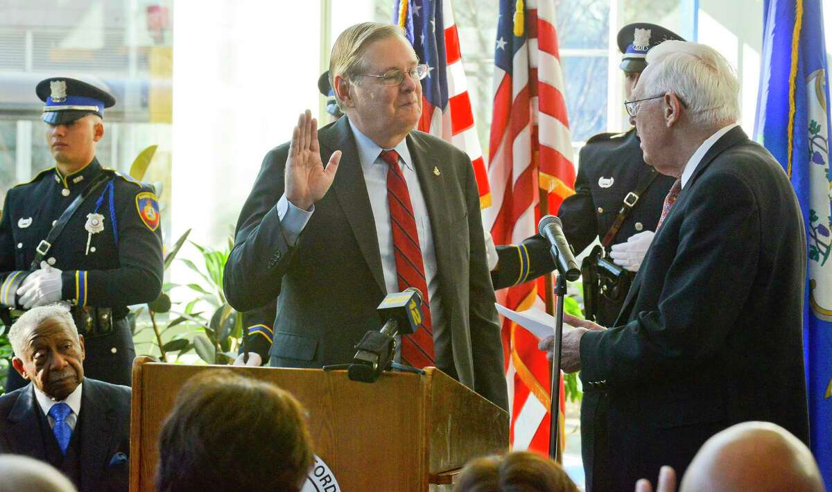 Stamford Mayor David Martin takes the oath of office from his father, Retired Justice Gene Martin, as he is ceremonially sworn in for his second term on Friday, Dec. 1, 2017 in Stamford, Connecticut.