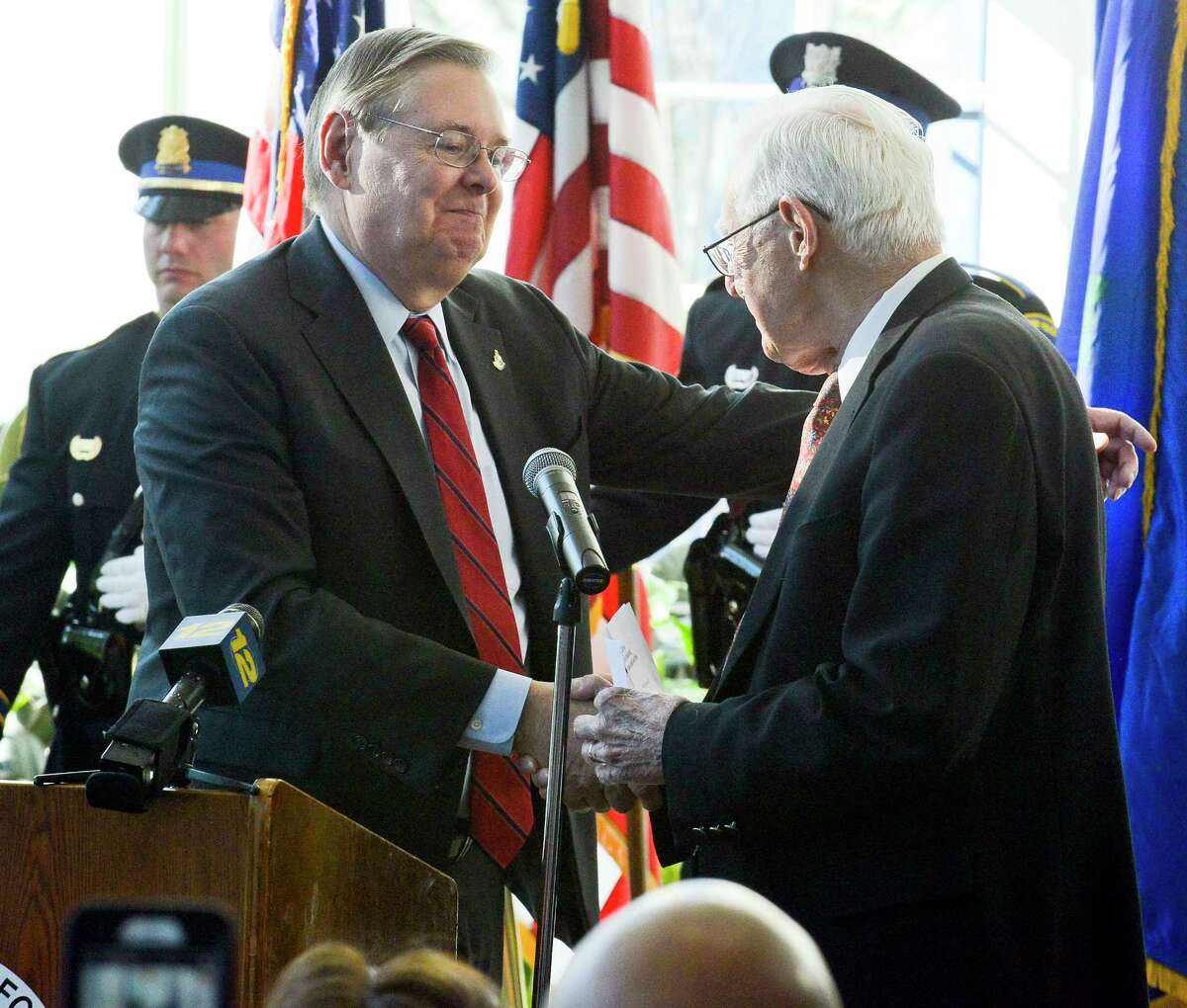 Stamford Mayor David Martin shakes the hand of his father Retired Justice Gene Martin, as he is ceremonially sworn in for his second term to office on Friday, Dec. 1, 2017 in Stamford, Connecticut.