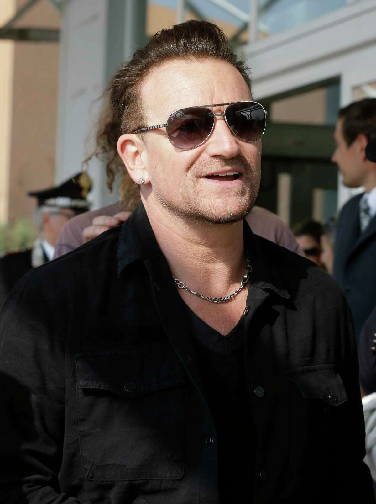 """FILE - In this Sept. 27, 2014 file photo, Bono smiles upon his arrival in Venice, Italy, to attend George Clooney's wedding ceremony. Bono says his ever-present sunglasses aren't a rock-star affectation ?- he has suffered from glaucoma for 20 years. told the BBC's """"Graham Norton Show"""" that he had the condition, but """"I have good treatments and I am going to be fine. (AP Photo/Luca Bruno, File) ORG XMIT: NYET553"""
