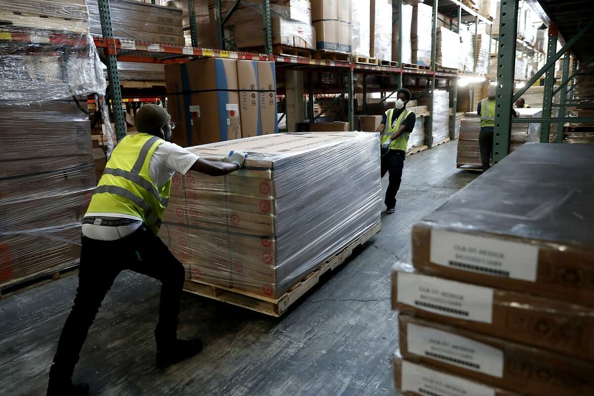 Workers move inventory at the huge warehouse of Zinus, an online mattress company headquartered in San Leandro, Ca., as seen on Friday Nov. 17, 2017.