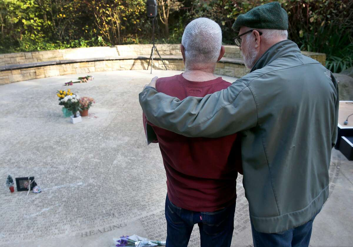 Gregory Curatolo (left) and his partner Sanford Dole gather to remember friends and loved ones who have died from AIDS at the Circle of Friends at the National AIDS Memorial in Golden Gate Park where former President Bill Clinton delivered the keynote address to commemorate World AIDS Day in San Francisco, Calif. on Friday, Dec. 1, 2017.