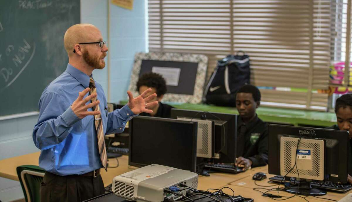 Instructor Kyle Dalton work with students during a sports marketing program at the Green Tech High Charter School Thursday Nov. 30, 2017 in Albany, NY. A new analysis shows charter schools are among the most racially segregated in the nation, but many say thatOs not a bad thing so long as they produce results. Green Tech High Charter School, pictured here, has a student body thatOs 97 percent black, but consistently produces the highest academic outcomes in the Albany City School District. (Skip Dickstein/ Times Union)