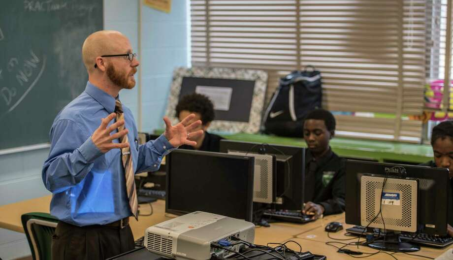 Instructor Kyle Dalton work with students during a sports marketing program at the Green Tech High Charter School Thursday Nov. 30, 2017 in Albany, NY.  A new analysis shows charter schools are among the most racially segregated in the nation, but many say thatOs not a bad thing so long as they produce results. Green Tech High Charter School, pictured here, has a student body thatOs 97 percent black, but consistently produces the highest academic outcomes in the Albany City School District. (Skip Dickstein/ Times Union) Photo: SKIP DICKSTEIN / 20042268A