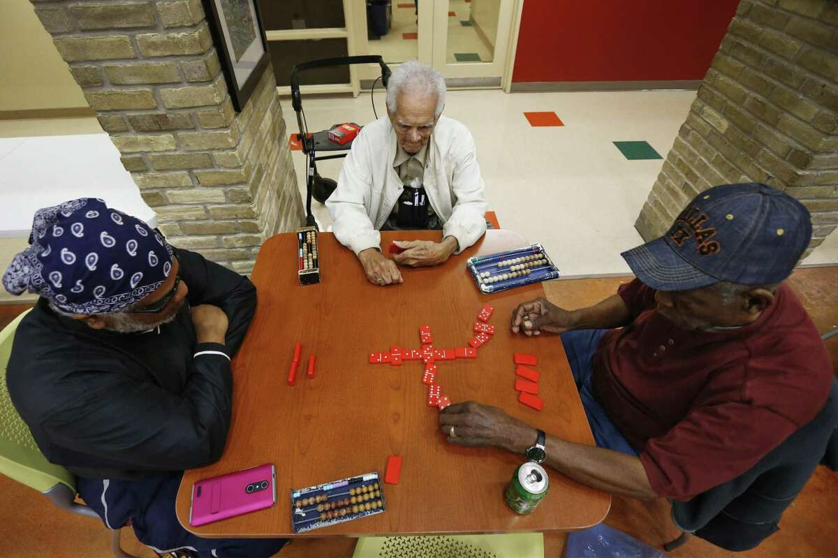 Charles Word (from left), Mack Thomas and August Felder play a round of dominoes after lunch provided by the city's Health and Human Services division at the Claude Black Community Center.
