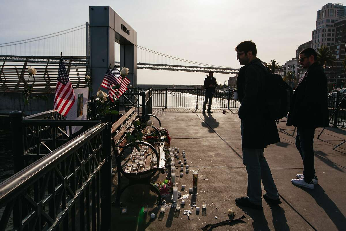 """Passersby on Pier 14 in San Francisco on December 1, 2017, following the acquittal of Garcia Zarate for the murder of Kate Steinle on July 15, 2015. A memorial was erected the previous evening by a group identifying itself as the """"Bay Area Alt Right."""""""