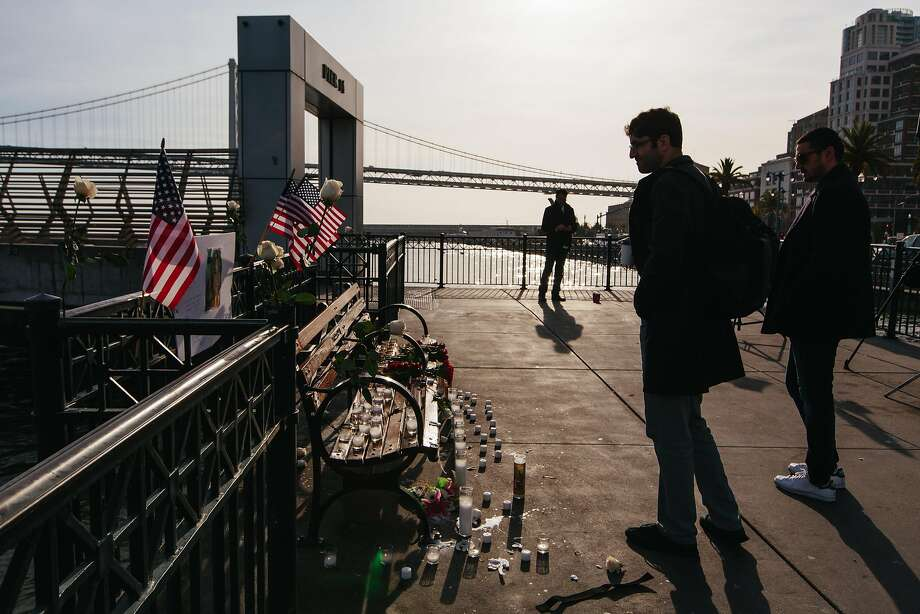 Visitors to Pier 14 in San Francisco pass a memorial to Kate Steinle put up at the site of her shooting death. Photo: Peter Prato, Special To The Chronicle
