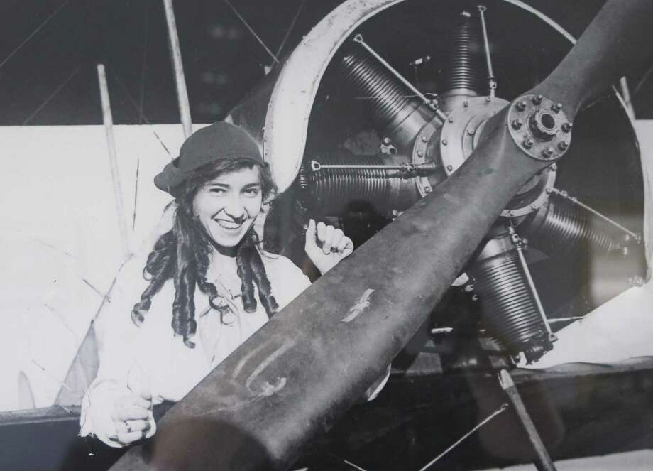 A copy of a 1916 photo hanging in the Stinson Municipal Airport terminal shows Katherine Stinson standing next to a plane at what was then Stinson Field. Photo: Express-News Archives / © 2015 San Antonio Express-News