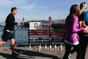 "Passersby on Pier 14 in San Francisco on December 1, 2017, in front of a memorial erected the previous evening by a group identifying itself as the ""Bay Area Alt Right"" following the acquittal of Garcia Zarate for the murder of Kate Steinle on July 15, 2015."