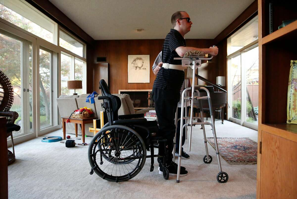 Sam Maxwell on Wednesday November 29, 2017, performs physical therapy standing with his caregiver Ernest Mena. Maxwell is thought to be the last person to make it out of the Ghost Ship alive. A year after the fire, he's currently re-learning how to talk and walk, at his parents house in Stockton, Calif.