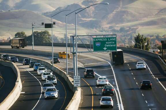 Morning commuters drive south passing a sign for an express lane on the Highway 237-880 interchange in Milpitas, Calif., on Monday, Nov. 27, 2017.