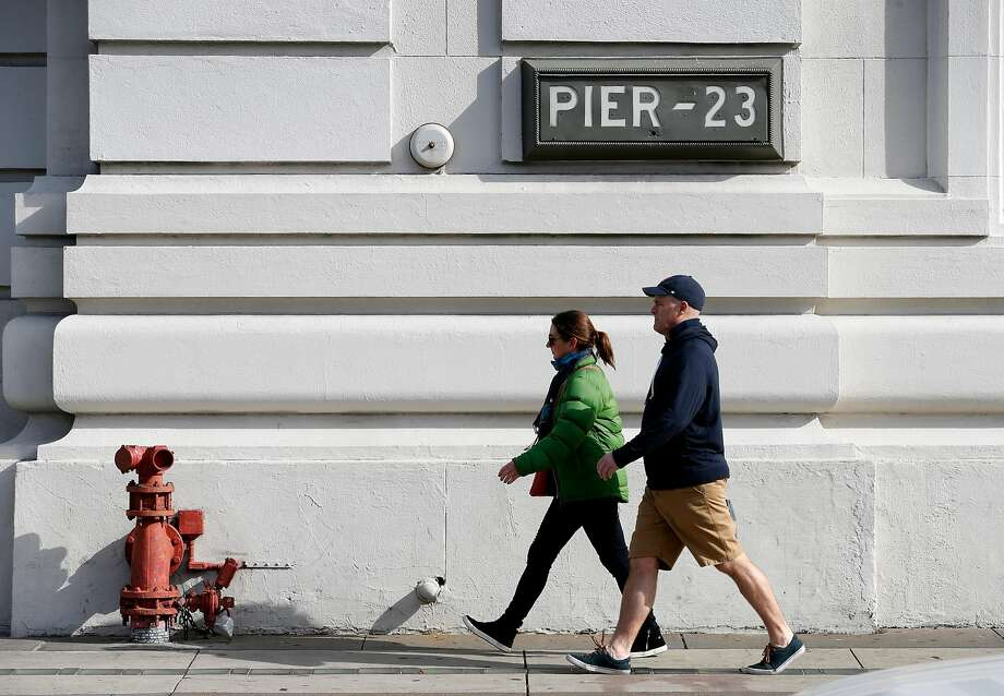People stroll past Pier 23, a site that Supervisor Aaron Peskin proposed then dropped for a homeless Navigation Center. Photo: Paul Chinn, The Chronicle