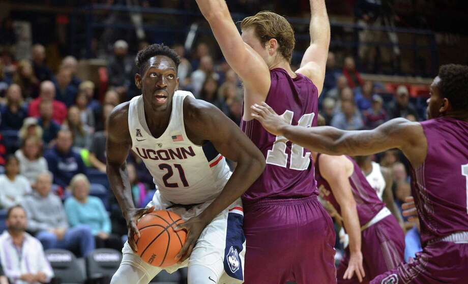 UConn's Mamadou Diarra, left, looks for room against Colgate earlier this season. Photo: Peter Casolino / Hartford Courant / Hartford Courant