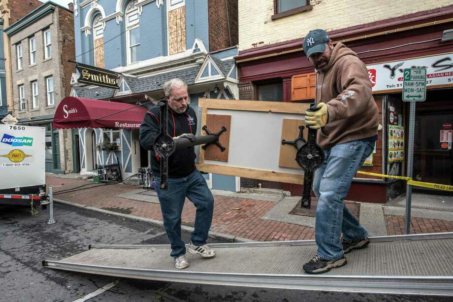 Workers remove useable furniture from Smith's Restaurant after a multi-alarm fire consumed three buildings and damaged at least 17 others last night on Remsen and surrounding streets on Friday, Dec 1, 2017, in Cohoes, N.Y.  (Skip Dickstein/ Times Union) Photo: SKIP DICKSTEIN / 20042291A