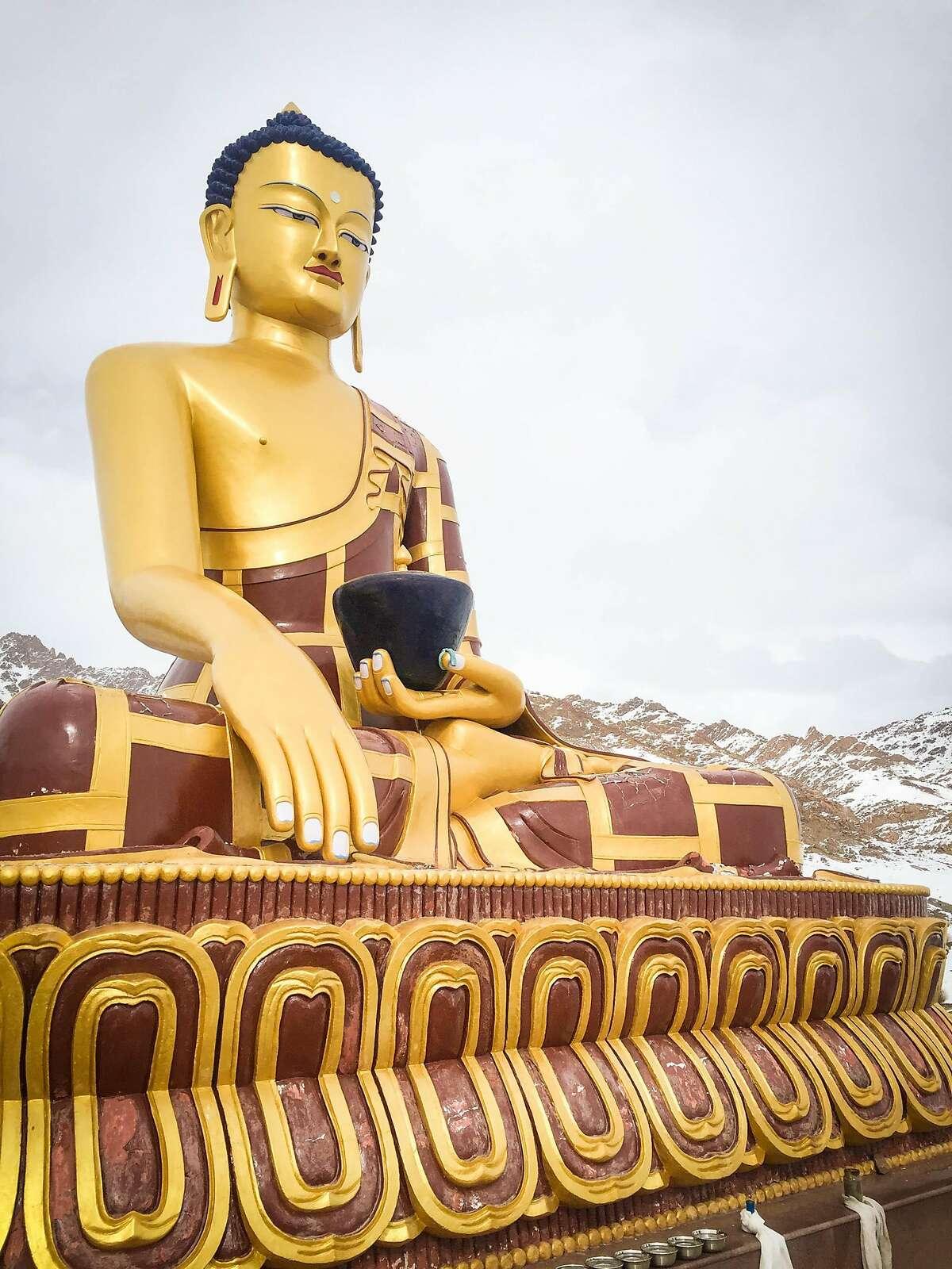 A giant, golden Buddha tops a hill in Hemis Shukpachan.