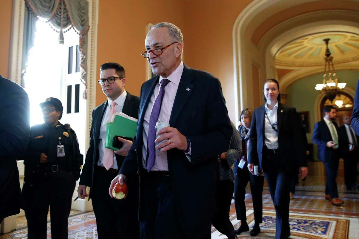 Senate Minority Leader Sen. Chuck Schumer of N.Y., center, walks through the Capitol, Friday, Dec. 1, 2017, on Capitol Hill in Washington. (AP Photo/Jacquelyn Martin) ORG XMIT: DCJM104