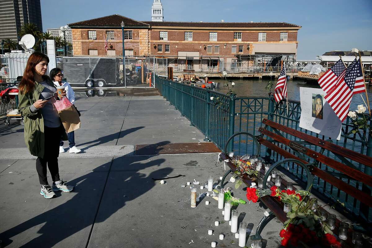 Kat Egan, of Brooklyn, New York, pauses to look at a memorial for Kate Steinle at Pier 14 on Friday, December 1, 2017 in San Francisco, Calif. Much of the shrine appeared to have been started by a self-proclaimed
