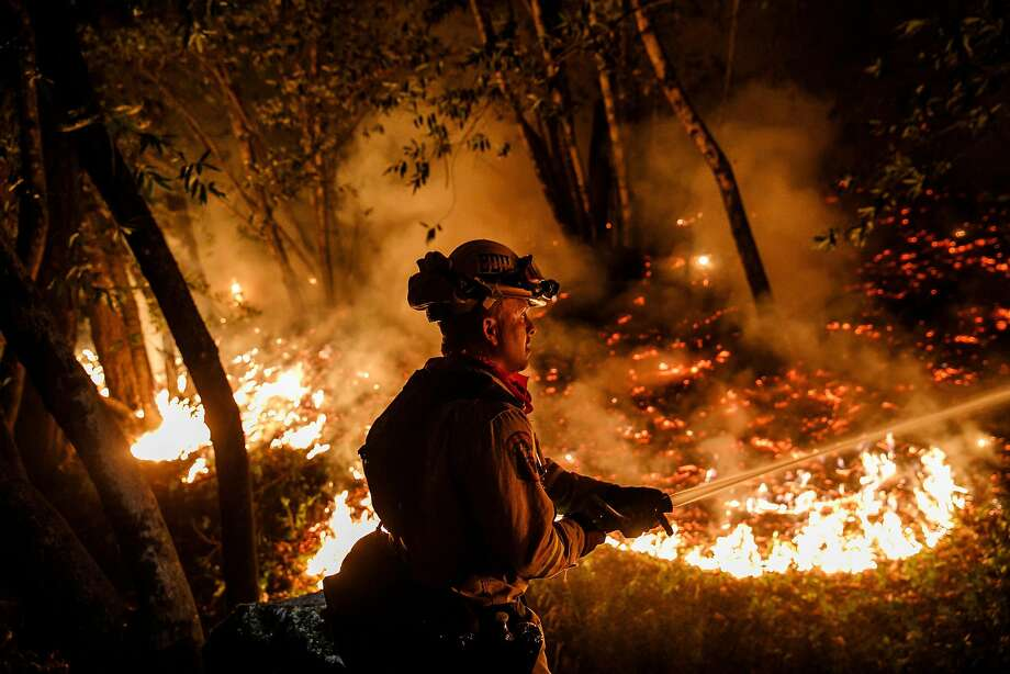 Firefighter Mario Topete attacks flames as his unit tries to prevent a fire from crossing Highway 29 north of Calistoga on Oct. 12, 2017. Photo: Marcus Yam, TNS