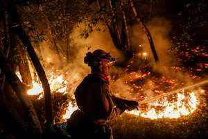Firefighter Mario Topete attacks flames as his unit tries to prevent a fire from crossing Highway 29 north of Calistoga on Oct. 12, 2017. (Marcus Yam/Los Angeles Times/TNS)