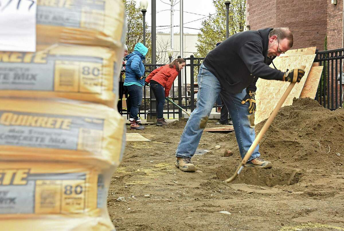 Brian Delaney, facilities director for Commission on Economic Opportunity, digs a hole as a team of volunteers from CAP COM Federal Credit Union and the CAP COM Cares Foundation donate their time and effort to rehabilitate one of two of CEOOs Head Start playgrounds at CEOOs Community Resource Center on Friday, Dec. 1, 2017 in Troy, N.Y. (Lori Van Buren / Times Union)