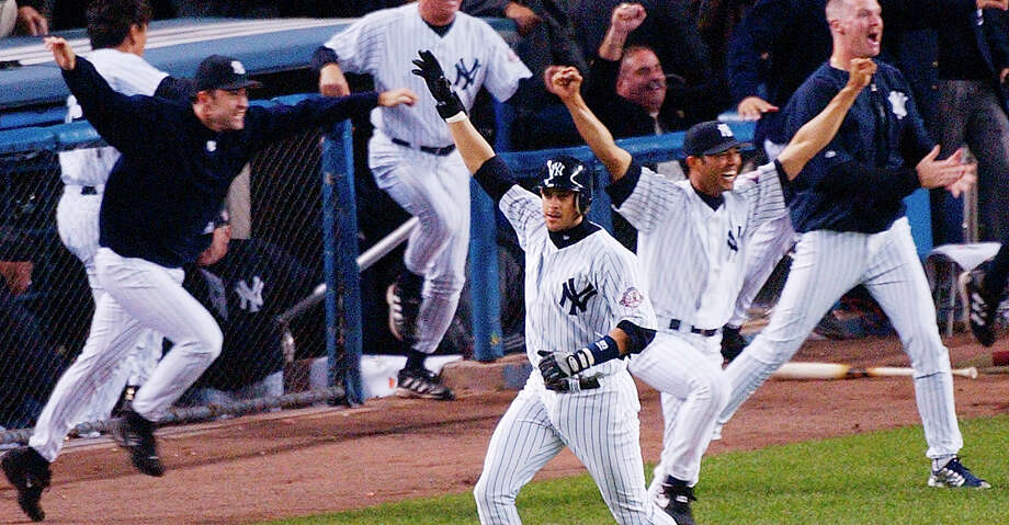 FILE - In this Oct. 16, 2003, file photo, New York Yankees' Aaron Boone, center, celebrates after hitting a solo home run in the 11th inning to beat the Boston Red Sox in Game 7 of the American League Championship Series in New York. Boone became the first person with no experience as a manager of coach to interview to become Joe Girardi's successor with the New York Yankees. The 44-year-old interviewed Friday, Nov. 17, 2017, becoming the fourth to go through the process after Yankees bench coach Rob Thomson, former Cleveland and Seattle manager Eric Wedge, and San Francisco bench coach Hensley Meulens. (AP Photo/Bill Kostroun, File) Photo: BILL KOSTROUN/Associated Press