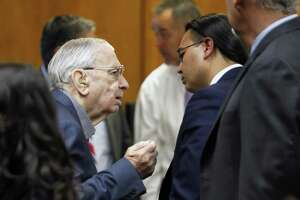 John Feit talks with one of his defense attorneys, O. Rene Flores, after the 92nd state District Court recessed for the day in Feit's trial in the 1960 killing of Irene Garza.