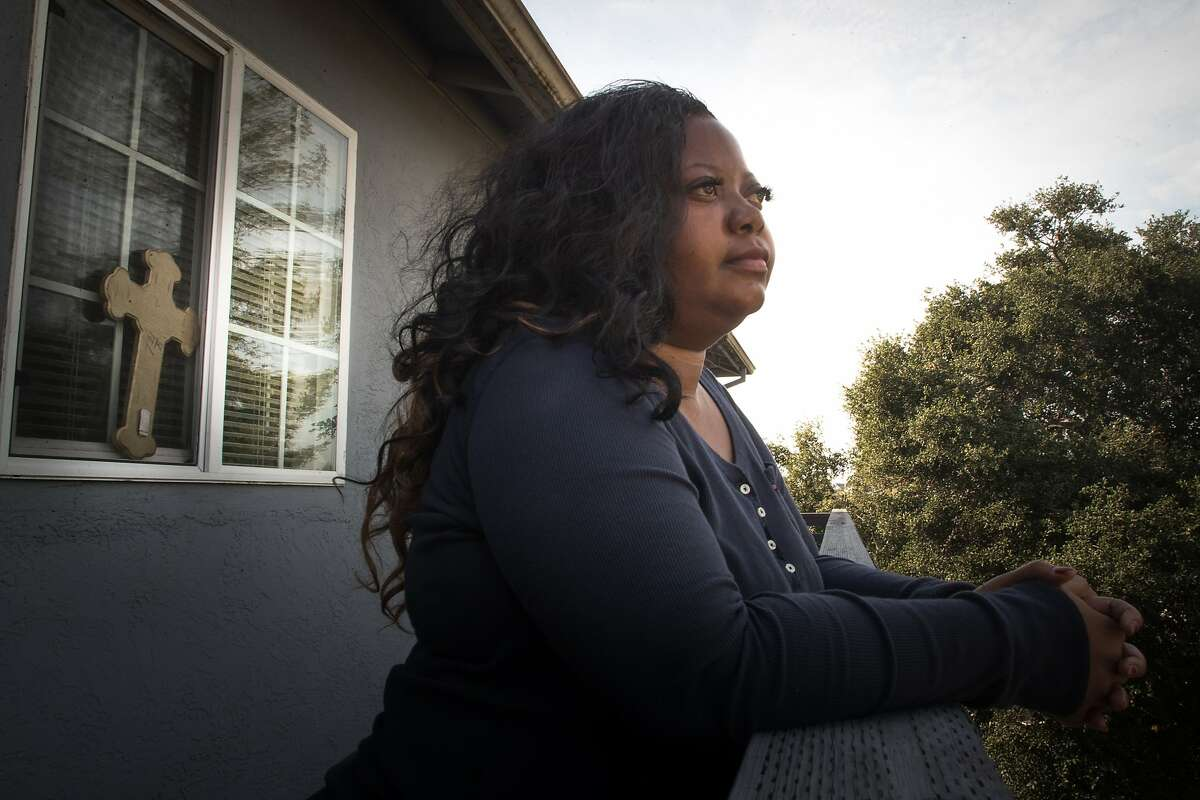 Tri-Nu Little, 38, on the balcony of her two-bedroom apartment in Oakland. Catholic Charities helped her connect with the Season of Sharing.