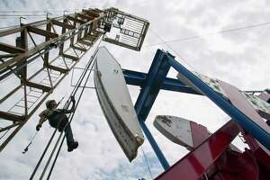 In this July 26, 2011, file photo, a worker hangs from an oil derrick outside of Williston, N.D. State data show that 1 billion barrels of oil have been produced from the rich Bakken shale formation in western North Dakota and eastern Montana. Data show that North Dakota has tallied 852 million barrels of Bakken crude, and Montana has produced about 151 million barrels. (AP Photo/Gregory Bull, File)