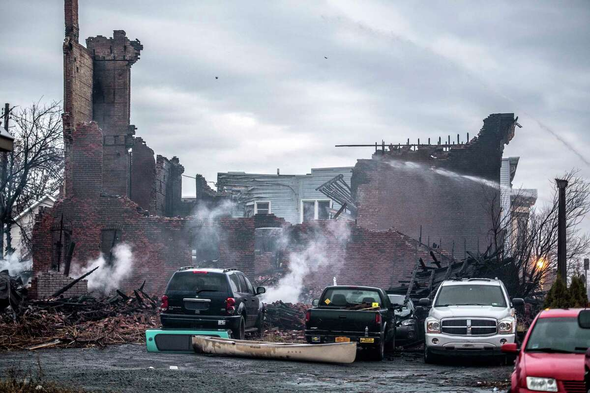 Firefighters wet down rubble and hot spots the morning after a multi-alarm fire consumed three buildings and damaged at least 17 others on Remsen and surrounding streets Friday Dec 1, 2017 in Cohoes, NY. (Skip Dickstein/ Times Union)