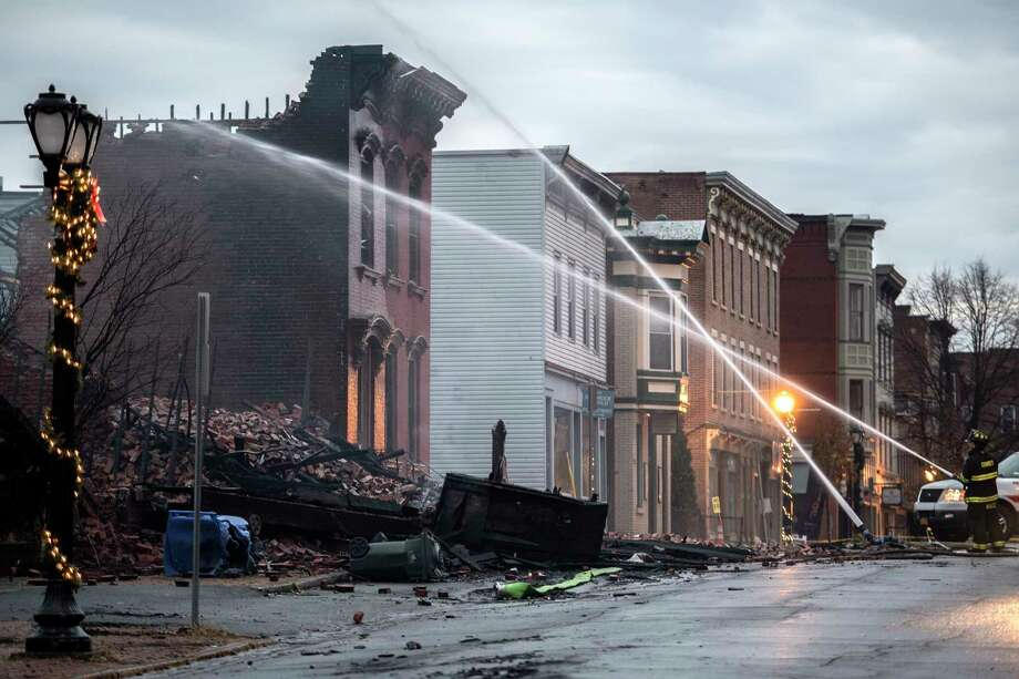 Firefighters wet down rubble and hot spots the morning after a multi-alarm fire consumed three buildings and damaged at least 17 others on Remsen and surrounding streets Friday Dec 1, 2017 in Cohoes, NY.  (Skip Dickstein/ Times Union) Photo: SKIP DICKSTEIN / 20042291A