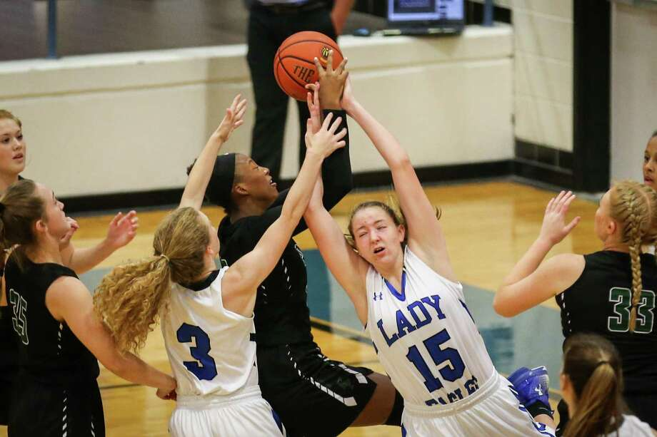 Kingwood Park's Samantha Mathews (15) and Skylar Patton (3) battle for a rebound with Kingwood Park's Allie Byrd (12) during the high school girls basketball game on Friday, Dec. 1, 2017, at New Caney High School. (Michael Minasi / Houston Chronicle) Photo: Michael Minasi, Staff Photographer / © 2017 Houston Chronicle
