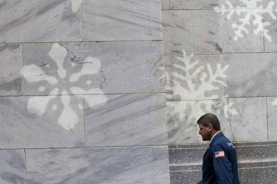 A broker passes snowflake lighting on the New York Stock Exchange's facade.  Photo: Mary Altaffer, STF / Copyright 2017 The Associated Press. All rights reserved.