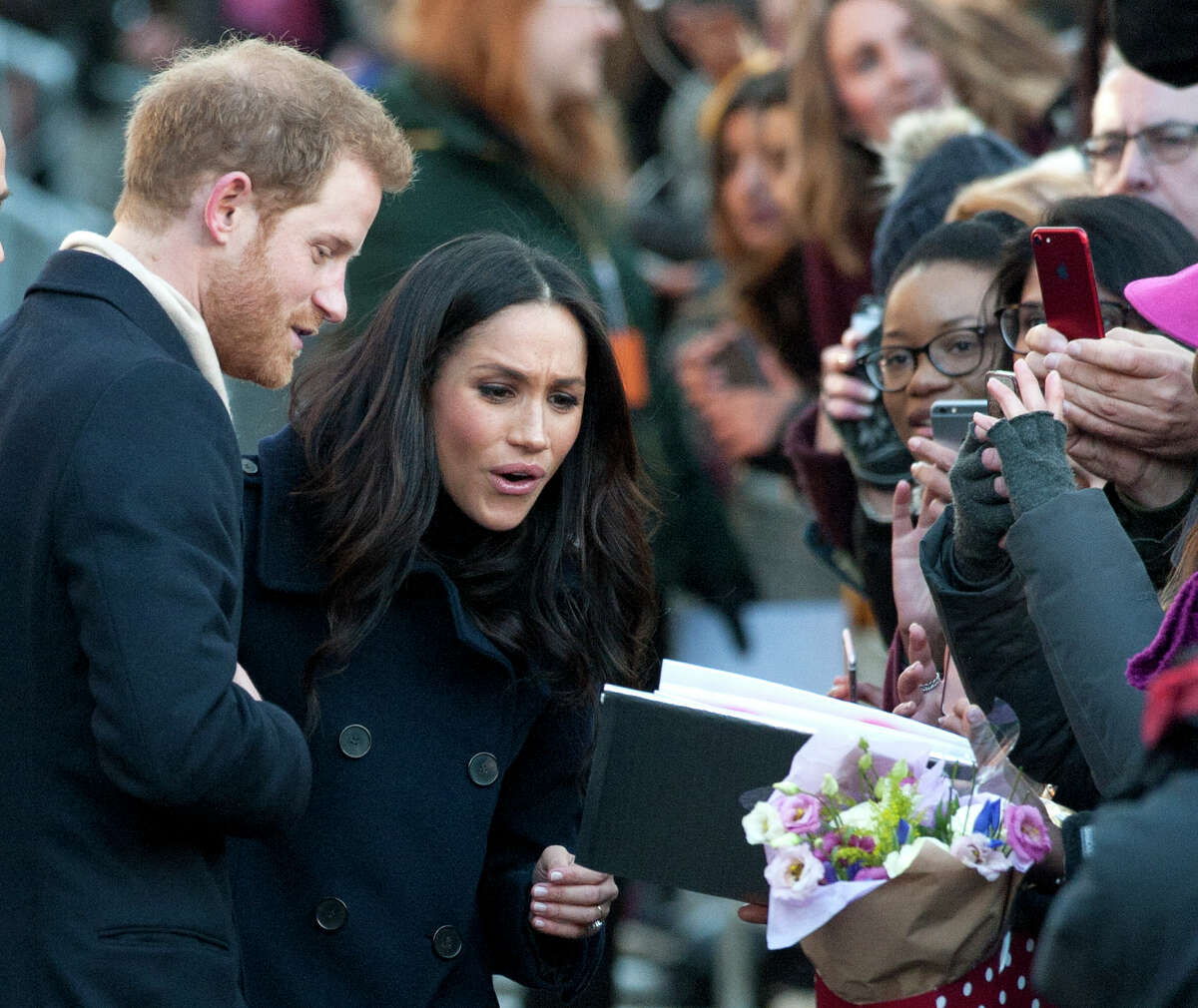 Britain's Prince Harry and his fiancee Meghan Markle, on their first official public engagement, take part in a walkabout en route to visiting the Terrence Higgins Trust World AIDS Day charity fair at the Contemporary Centre in Nottingham, England, Friday Dec. 1, 2017. It was announced on Monday that Prince Harry and American actress Meghan Markle are engaged and will marry in the spring of 2018. (AP Photo/Rui Vieira) ORG XMIT: BRV103