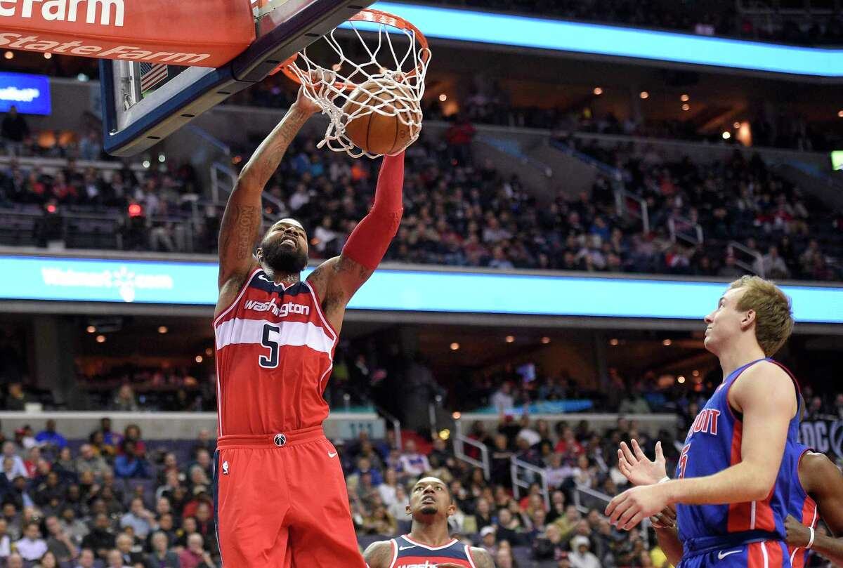 Washington Wizards forward Markieff Morris, left, dunks in front of Detroit Pistons guard Luke Kennard, right, during the second half of an NBA basketball game, Friday, Dec. 1, 2017, in Washington. Wizards guard Bradley Beal is at center. The Wizards won 109-91. (AP Photo/Nick Wass) ORG XMIT: VZN109