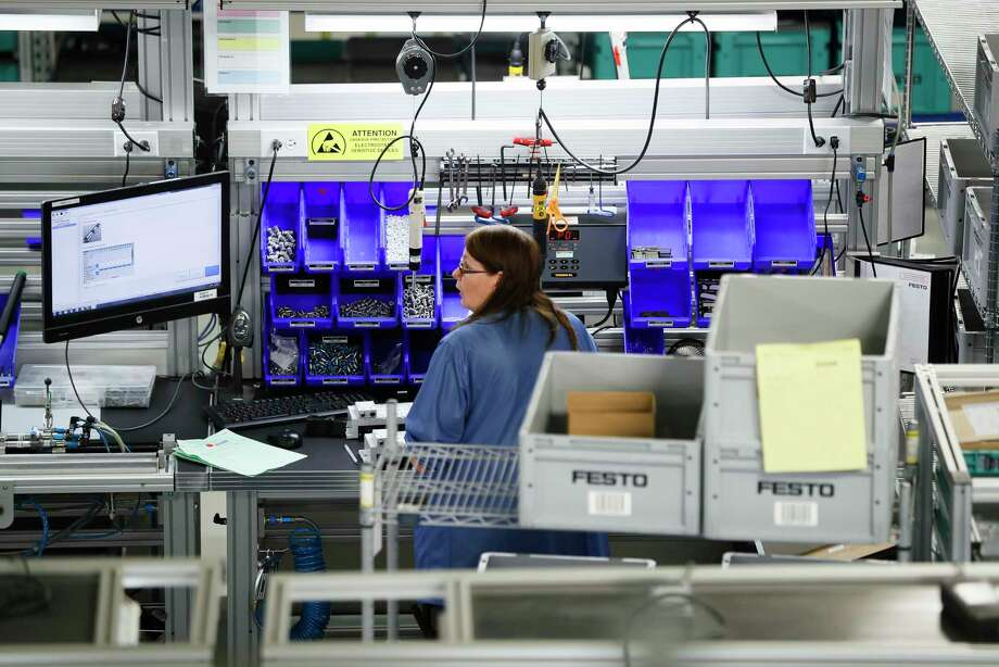 An employee works at the Festo distribution center in Mason, Ohio. A trade association said 14 of 18 manufacturing industries expanded in November.  Photo: John Minchillo, STF / AP