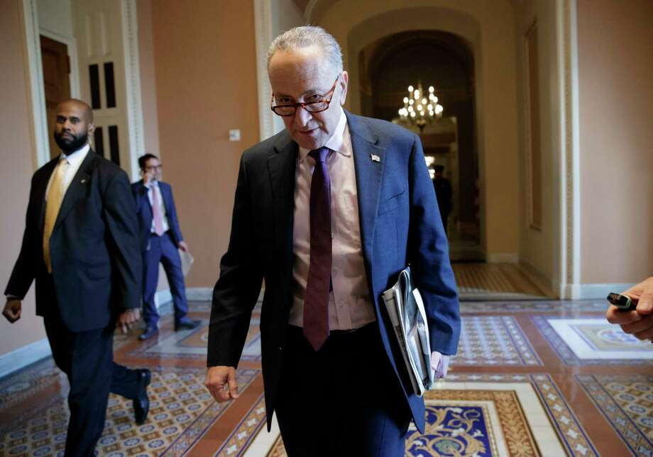 Senate Minority Leader Chuck Schumer, D-N.Y., walks to his office as Majority Leader Mitch McConnell, R-Ky., and Republican lawmakers meet behind closed doors to advance the GOP overhaul of the tax code, on Capitol Hill in Washington, Friday, Dec. 1, 2017. (AP Photo/J. Scott Applewhite) Photo: J. Scott Applewhite / Copyright 2017 The Associated Press. All rights reserved.
