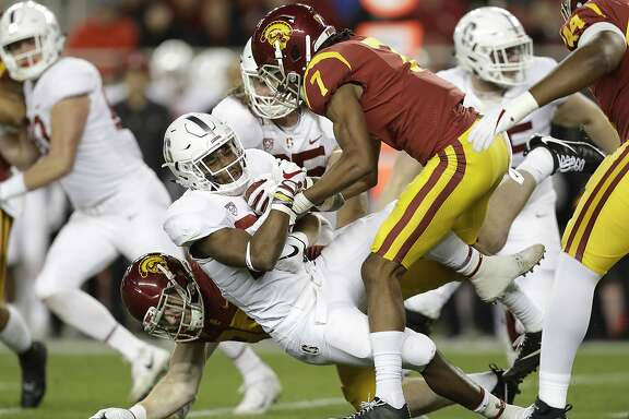 Stanford running back Bryce Love, center, is tackled by Southern California defenders during the first half of the Pac-12 Conference championship NCAA college football game in Santa Clara, Calif., Friday, Dec. 1, 2017. (AP Photo/Marcio Jose Sanchez)