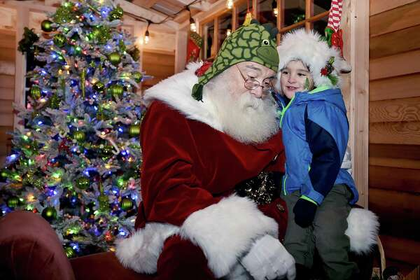 Milford resident Hayden Kalb, 3, tells Santa Rick George what is on his Christmas list after George had fun exchanging hats at the 16th Annual Downtown Milford Lamplight Stroll, Friday, Dec. 1, 2017, on River Street.