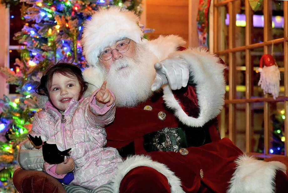 "For her first time meeting Santa, Orange resident Anya Pagter, 3, points to her father, Jerry Pagter when Santa Rick George asks Anya, ""Is that your Daddy taking our picture,"" on River Street at the 16th Annual Downtown Milford Lamplight Stroll, Friday, Dec. 1, 2017. Photo: Catherine Avalone / Hearst Connecticut Media / New Haven Register"