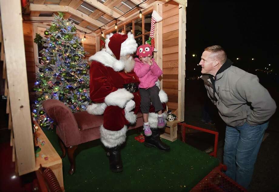 """Milford resident Bob Young tries to coax a response from his three-year-old daughter Lyla Young when Santa Rick George asked, """"So whats on your Christmas list"""" at the 16th Annual Downtown Milford Lamplight Stroll, Friday, Dec. 1, 2017. Photo: Catherine Avalone / Hearst Connecticut Media / New Haven Register"""