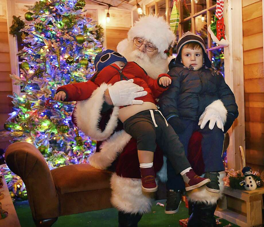 Pio Imperati, 3 seems to ignore his one-year-old brother Luca's reaction to having their picture taken with Santa Rick George at the 16th Annual Downtown Milford Lamplight Stroll, Friday, Dec. 1, 2017. Photo: Catherine Avalone / Hearst Connecticut Media / New Haven Register
