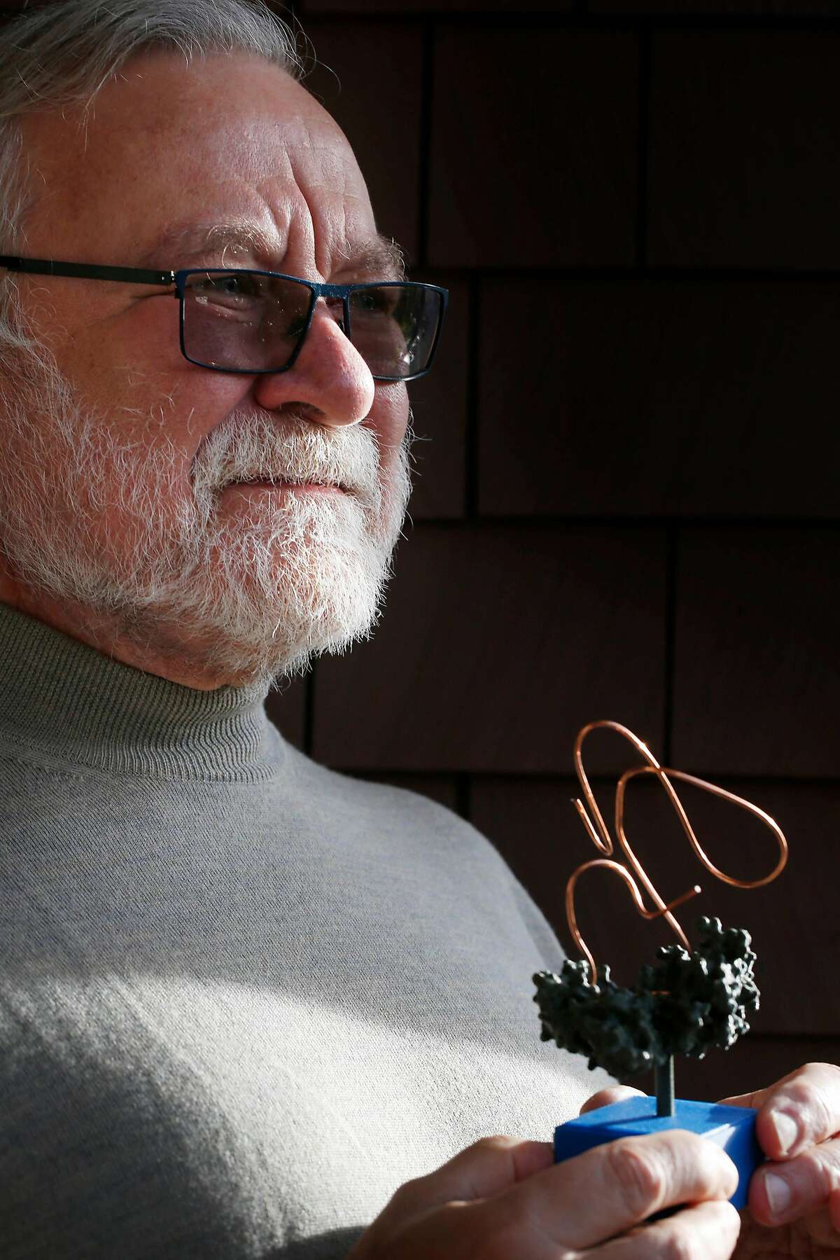 Peter Walter, UCSF biochemist, holds a model of the Ire1 binding to an unfolded protein as he stands for a portrait on Friday, December 1, 2017 in San Francisco, Calif. Walter is one of this year's recipients of The Breakthrough Prize.