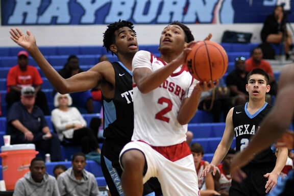 Crosby senior guard Shemar Johnson (2) drives to the hoop against a Sam Rayburn defender during their pool play matchup at the Sam Rayburn tournament at SRHS on Dec. 1, 2017. (Photo by Jerry Baker/Freelance)
