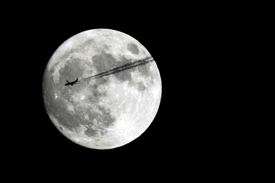 "An airplane flies past the moon above Stamford, Conn. on Sunday, Nov. 13, 2016. Sunday, Dec. 3, 2017, will be residents the only chance this year to see the ""supermoon."" Photo: Michael Cummo / Hearst Connecticut Media / Stamford Advocate"