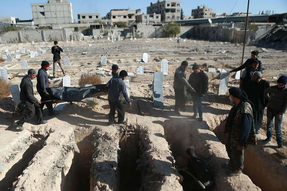Syrians bury the victims of an air strike on the rebel-held town of Arbin on the outskirts of Damascus. The government and opposition resumed peace talks in Geneva on Tuesday. Photo: ABDULMONAM EASSA, AFP/Getty Images