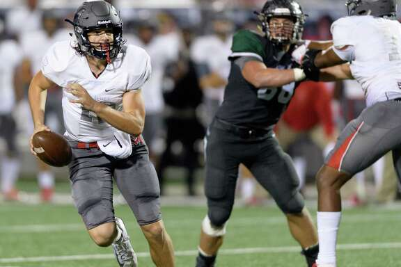 Kason Martin (12) of Manvel rolls out to pass in the first half against  Cedar Park in a Class 5A playoff game Friday in Waller.