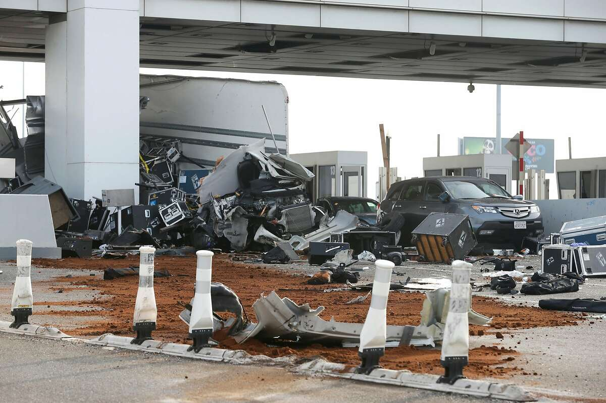 Debris is spread across several westbound lanes at the Bay Bridge toll plaza after a truck rammed through toll booth 14, killing the toll collector inside, before daybreak in Oakland, Calif. on Saturday, Dec. 2, 2017. The two occupants of the truck were reportedly ejected from the vehicle.